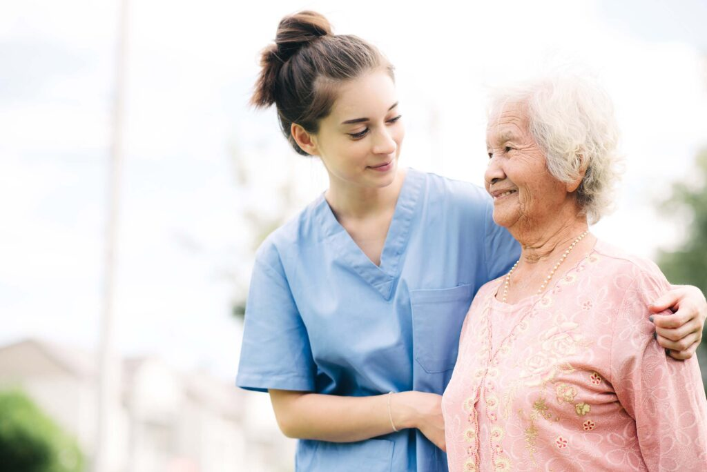 Female caregiver helping elderly woman walk